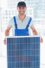 le bureau solaire bricoleur de sourire tenant le panneau solaire dans le bureau