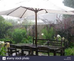 Rainy Summer Weather In A Garden With Table Chairs And Sunshade