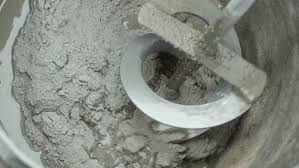 worker pour water on mixture in and mix tile adhesive glue
