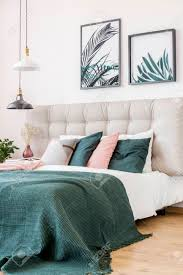 nahaufnahme rosa und grünen kissen auf bett im blumenschlafzimmerinnenraum mit blattposter und schwarzweiss le