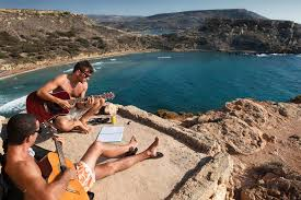 Picture Of Young Men Playing Guitar Above The Ghajn Tuffieha Beach Malta