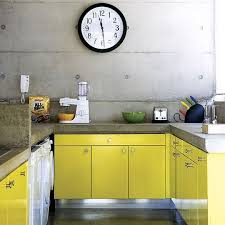 An Industrial Kitchen With Lemon Yellow Cabinets Concrete Walls And Countertops