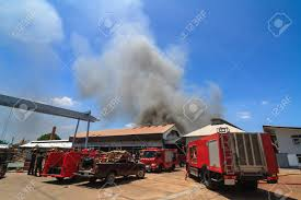 Fire Truck And Burning Warehouses With Black Smoke Against Blue ...