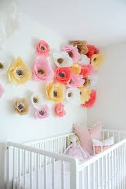 Bring Freshness And Zest To Your First Nursery Room With These Dainty Colored Paper Flower Decorations Adorning The Walls