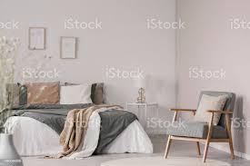 holz sessel neben bett mit decke und kissen in weiße schlafzimmer inneren echtes foto stockfoto und mehr bilder beige
