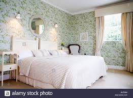 wall lights above bed with bed cover in traditional country