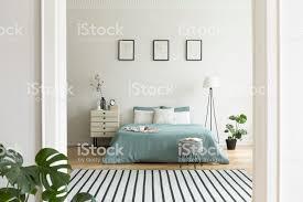ein blick aus einem anderen raum in einem pastell schlafzimmer innenraum mit einem großen bett in der mitte und eine le und eine nacht neben