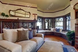vintage stil wohnzimmer mit beige sofa und antiken holzschrank mit blick auf gemütliche sitzecke