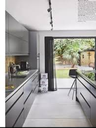 Kitchen with white cupboard doors and designer pendant lamp above