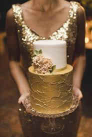 Beautiful Bride Or Bridesmaid In Sequined Gold Floor Length Gown Holding The Two Tiered And Ivory Wedding Cake
