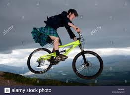 mountain bike range in kilt jumping on his mountain bike on the downhill