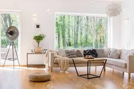 entworfene le geflochtener hocker und kleiner baum im geräumigen wohnzimmer mit blick auf wald