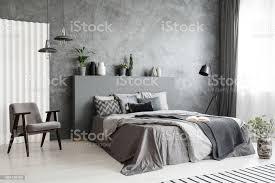 moderne grau schlafzimmer innenraum mit großem bett mit kissen und bettwäsche bequemer sessel neben dem bett echtes foto stockfoto und mehr bilder