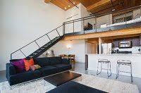 offenes wohnzimmer mit theke zur küche und treppenaufgang