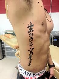 Black Ink Kanji Tattoos On Rib Side For Men