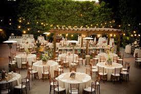 Rustic Wedding In Garden With Lights And Wooden Tables Covered White Table Cloths