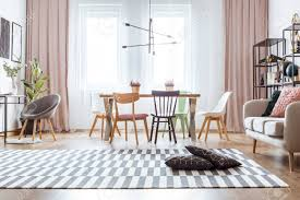 schwarze kissen auf gemusterten teppich und rosa vorhänge in gemütlichen wohnzimmer interieur mit stühlen am esstisch in der nähe sofa