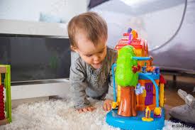 foto auf lager niedliches kleines baby spielt mit spielzeug im wohnzimmer auf einem teppichboden