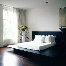 Black Platform Double Bed A Grey Satin Bedspread And Glossy Wooden Floor