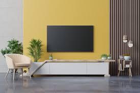 wohnzimmer führte fernsehen auf gelber wand mit sessel und