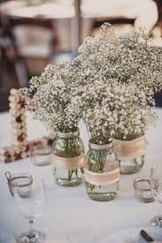 Several Jars Wrapped With Burlap And Babys Breath For A Beautiful Table