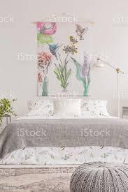 stoff mit blumen hängen weiße wand innen helle schlafzimmer mit metallle doppelbett mit floral blätter und graue decke in das realistische foto
