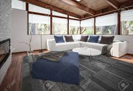 blick auf geräumiges wohnzimmer mit weißem sofa boden teppich und blauen sitzpuff am kamin und panoramafenster ecke 3d rendering