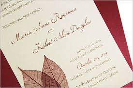 Cream fall wedding invitation decorated with dried leaves