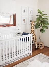 babyzimmer in weiß kuscheltier giraffe neben dem babybett