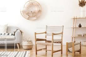 stilvolles und gemütliches wohnzimmerinterieur mit vielen rattanaccessoires designsessel grauem sofa und holzregal koreanischer stil der