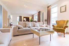 licht und ein gemütliches wohnzimmer mit einem bequemen sofa einen kleinen tisch und viktorianischen sessel