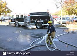 Female Firefighter Drags Hose With A Black Fire Truck In The Stock ...