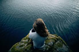 Image Of A Woman Sitting On Cliff Overlooking Water Contemplating Freedom