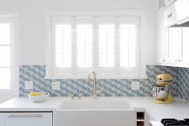 blue geometric tiles with white cabinets transitional kitchen