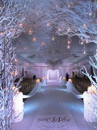 White Reception Winter Wedding Decor With Painted Tree Branches And Runners Also Small Gold Chairs Under Crystal Chandelier
