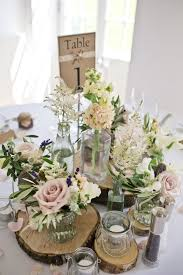 Centrepiece Of Rustic Tree Slices With Jars Pink Flower Stems