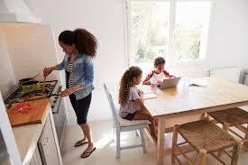 cuisine maman maman faisant cuire tandis que les enfants travaillent à la table