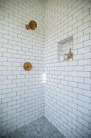 shower with white subway tiles and gray marble basketweave floor