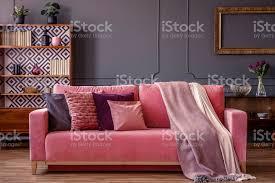 kissen und decken auf einem rosa samt sofa in einem luxuriösen grau wohnzimmer interieur mit holzmöbeln stockfoto und mehr bilder antiquität