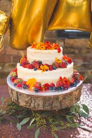 Semi Naked Wedding Cake Laden With Fruit On Rustic Tree Slice Stand