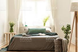 eco freundliche schlafzimmer mit einem bett gekleidet in grau und grün bettwäsche innenraum sonnigen fenster als hintergrund echtes foto stockfoto und