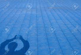 Shadow Of Man Who Show Extend The Fingers Heart Shape On Blue Rubber Flooring
