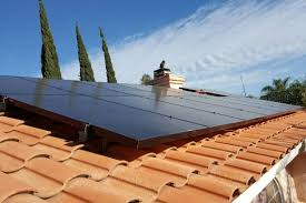 flat solar panels on a clay tile roof in riverside ground up