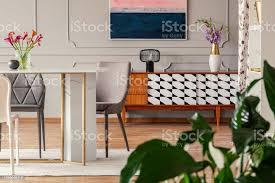antik holz sideboard mit einem muster und esszimmerstühle um einen marmor und goldenen tisch eines künstlerischen wohnung zimmer innen stockfoto und