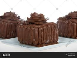 Three Square chocolate cake cupcakes on a chocolate candy bar frosted with frosting rose on top