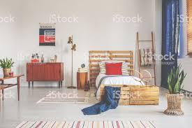 holzbett mit weißer bettwäsche und roten kissen im geräumigen schlafzimmer mit gestreiften teppich und retromöbeln echtes foto stockfoto und mehr