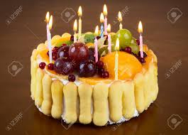 Happy birthday fruit cake with candles on wooden table background Stock