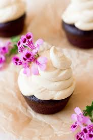 Vanilla Buttercream Frosting Swirled On Top Of Chocolate Cupcakes With Pink Flowers