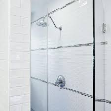 amazing walk in shower is filled with white brick tiles accented