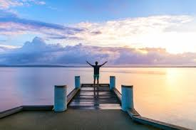 Man Standing With Outstretched Arms On A Jetty At Sunrise